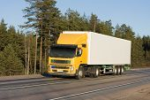 foto of moving van  - tractor trailer truck on background of trees of  - JPG