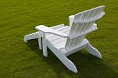 White adirondack lounge chair in green grass