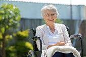 Happy senior woman sitting on wheelchair and recovering from illness. Handicapped mature woman sitti poster