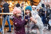 Happy Kid Girl And Young Beautiful Woman With Cup Of Steaming Hot Chocolate And Mulled Wine. Adorabl poster