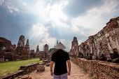 Man In Chinese Hat Standing Back Near The Ancient Ruins At Wat Mahathat In Ayutthaya Historical Park poster