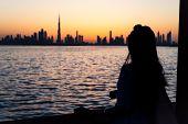 Woman Enjoying Dubai Landmark View At Sunset poster