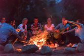 a group of happy young friends relaxing and enjoying  summer evening around campfire on the river ba poster