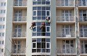 Three steeplejacks working on a newly built house