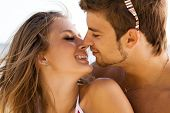 Young beautiful couple kissing at the sea shore