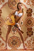 Beautiful woman posing with russian musical instrument balalaika over a traditional west-european carpet