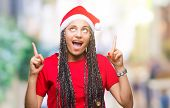 Young braided hair african american girl wearing christmas hat over isolated background amazed and s poster