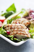 pic of gourmet food  - closeup of a healthy chicken salad with greens and pomme granate seeds and avocado - JPG