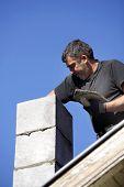 Mason building chimney
