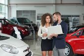 Manager Of Car Dealership Showing And Selling Automobile To Female Client. Handsome Man Wearing In D poster
