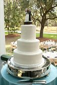 white wedding cake on silver tray at outside reception