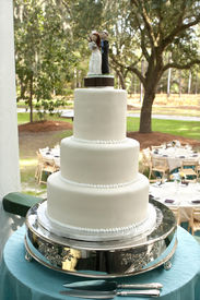 stock photo of wedding table decor  - white wedding cake on silver tray at outside reception - JPG