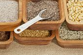 chia and other healthy seeds (gold and brown flax, hemp. pine nuts) in wooden bowl with measuring te