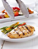 Summer grilling time - grilled chicken with vegetables with grill tongs
