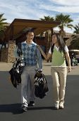 Full length of happy couple carrying golf bags walking out of building