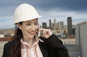 Happy female architect wearing hard hat talking on phone