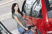 Happy woman refueling her car