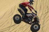 Постер, плакат: Квадроцикл Райдер перепрыгивая через песок в пустыне