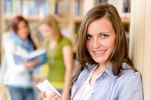 Happy female brunette student at library with books high school