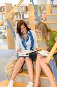 Brunette teenager with classmate studying at high school library stairs