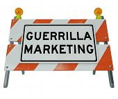 The words Guerrilla Marketing on a barricade or barrier to illustrate uncommon business tactics and campaigns for attracting customers and building awareness with underground methods