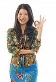 Mulher asiática em roupas kebaya mostrando sinal de mão ok
