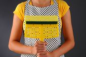 Closeup of a homemaker in an apron holding a sponge mop in front of her torso. Horizontal format over a light to dark background. Woman is unrecognizable.