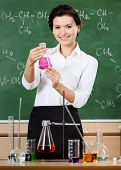 Smiley chemistry teacher holds a conical flask with purple liquid