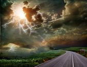stock photo of spring break  - The road through the meadow and the stormy skies - JPG