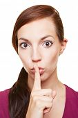 Young woman putting her index finger on her lips as silence symbol