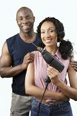 Happy African American couple with woman holding drill