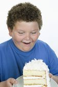 Obese teenage boy with a slice of cake isolated over white background