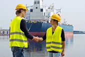 Female docker shaking hands with a male coworker in an industrial harbor, in front of a huge freight