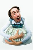 stock photo of greedy  - Portrait of greedy male raking in dollars and being glad - JPG