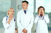 Three clinicians in white coats in shock