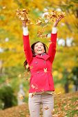 Happy fall woman throwing autumn leaves up in the air smiling blissful and cheerful in autumn forest. Young beautiful multicultural Caucasian / Asian woman model outside.