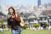Alamo Square San Francisco Tourist. Young traveler woman holding camera in Alamo Park by the Painted