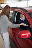 Businesswoman presenting the car to a client in a dealership