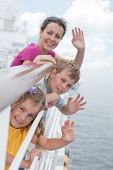Mother with her children stand on deck of large passenger ship near handrails and waving their hands, focus on daughter