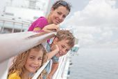 Mother with her children stand on deck of large passenger ship near handrails, focus on girl