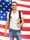 stock photo of citizenship  - bright picture of travelling student with backpack and book over american flag - JPG