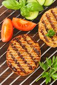 grilled meat burger with tomatoes and cucumbers on a grid