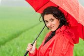 Smiling woman looking at camera during rainfall posing with umbrella