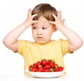 Little boy refuses to eat strawberries and holding his head with hands, isolated over white