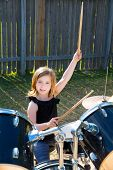 Drummer blond kid girl playing drums in the backyard lawn