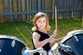 Chica chico rubio de baterista tocando la batería en el césped del jardín