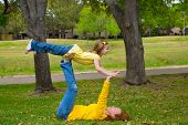 Daughter and mother playing keeping balance lying on park lawn outdoor