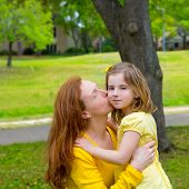 Mother kissing her blond daughter in green park outdoor dressed in yellow