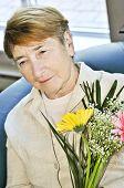 Triste anciana con flores