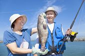 stock photo of grouper  - asian senior couple fishing and showing big grouper - JPG